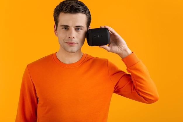 Stilvoller lächelnder junger mann im orangefarbenen pullover, der drahtlosen lautsprecher glücklich hört, musik zu hören, die spaß auf orange hat Kostenlose Fotos