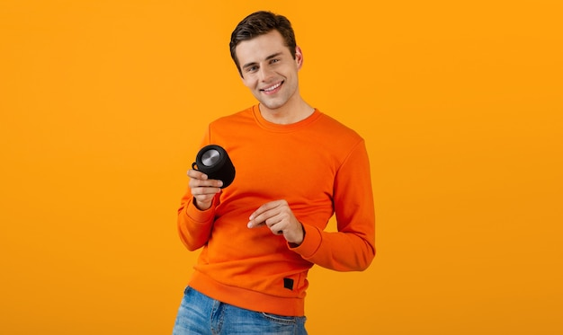 Stilvoller lächelnder junger mann im orangefarbenen pullover, der drahtlosen lautsprecher glücklich hört, musik zu hören, die spaß auf orange hat
