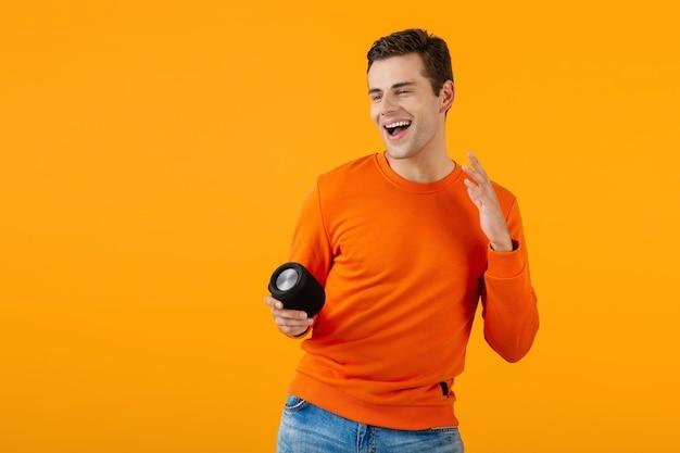 Stilvoller lächelnder junger mann im orangefarbenen pullover mit drahtlosem lautsprecher, der gerne musik hört