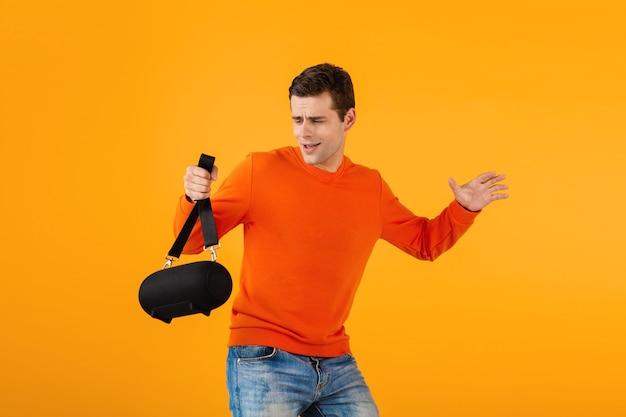 Stilvoller lächelnder junger mann im orangefarbenen pullover mit drahtlosem lautsprecher, der gerne musik hört Kostenlose Fotos