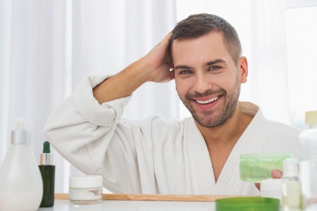 Stilvoller look. positiver gutaussehender mann, der eine flasche haargel hält, während er vor dem spiegel steht