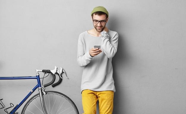 Stilvoller männlicher radfahrer, der grünen hut und brillen trägt, die online-kommunikation auf handy genießen, sein fahrrad, das neben ihm steht