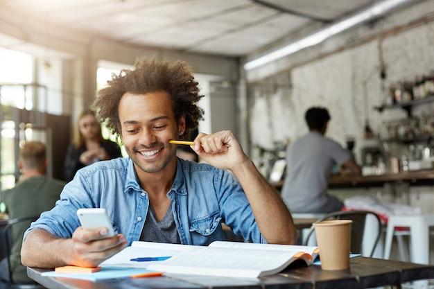 Stilvoller männlicher student, der an der cafeteria arbeitet