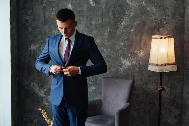 Stilvoller mann befestigt den knopf an der jacke. junger mann, der im weißen hemd und im grauen anzug nahaufnahme innen trägt. mann versucht einen business-anzug im laden. porträt des gutaussehenden mannes im grauen anzug und in der roten krawatte