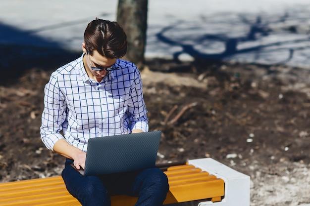 Stilvoller mann, der an laptop an der straße arbeitet