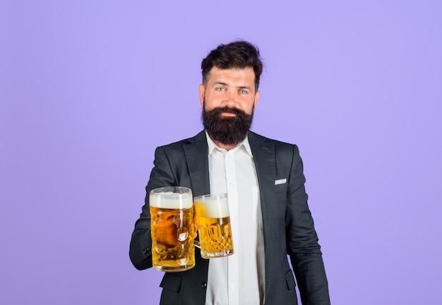 Stilvoller mann, der bier aus glasbier trinkt, hält eine tasse bier mit schaumalkohollager und dunkel