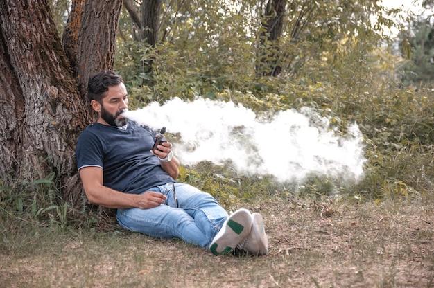 Stilvoller mann, der eine elektronische zigarette auf dem boden genießt