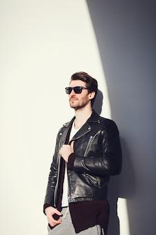 Stilvoller mann, der eine schwarze lederjacke trägt