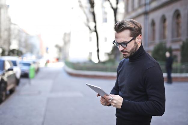 Stilvoller mann, der eine tablette auf der straße verwendet