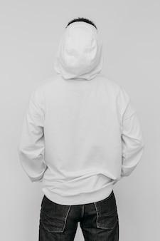 Stilvoller mann, der einen weißen kapuzenpulli trägt