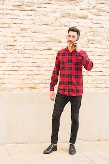 Stilvoller mann, der gegen die backsteinmauer spricht am handy steht