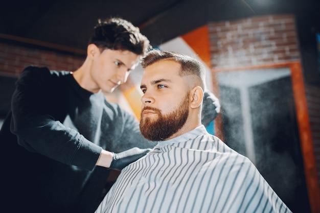 Stilvoller mann, der in einem friseursalon sitzt