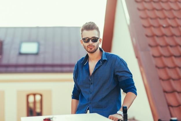 Stilvoller mann, der in tragendem hemd der straße steht
