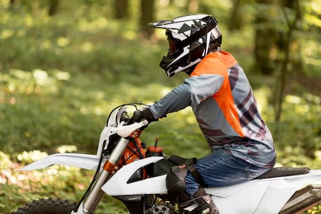 Stilvoller mann, der motorrad der seitenansicht reitet