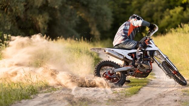 Stilvoller mann, der motorrad im wald reitet
