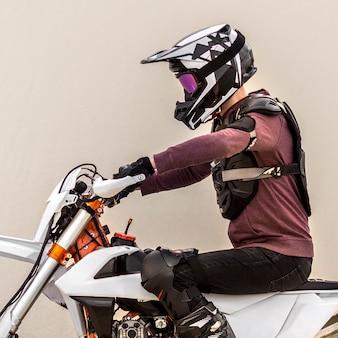 Stilvoller mann, der motorrad in der wüste reitet