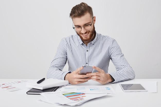 Stilvoller mann hat trendige frisur, die nachrichten auf smartphone schreibt
