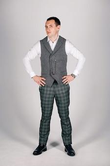Stilvoller mann im karierten anzug auf einem grauen hintergrund