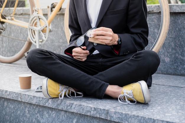 Stilvoller mann im schwarzen anzug und in den freizeitschuhen, die seine lesebrille draußen reinigen. hipster-person, die im stadtgebiet mit tasse kaffee vor seinem retro-rennrad sitzt