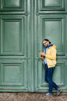 Stilvoller mann in der schwarzen kappe und im gelben anorak, die seitlich gegen den grünen hintergrund hält handy steht