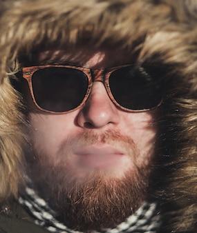 Stilvoller mann in der sonnenbrille bläst zigarettenrauch aus seinem mund