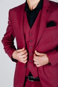Stilvoller mann in einer hochroten jacke auf einem hellen hintergrund