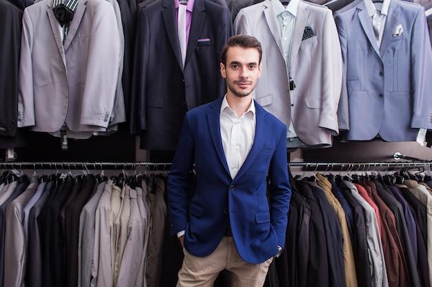 Stilvoller mann in einer kleiderboutique auf dem hintergrund der jacken