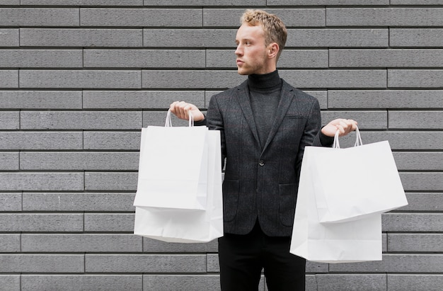 Stilvoller mann mit einkaufstüten in beiden händen