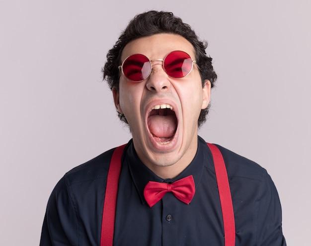 Stilvoller mann mit fliege, der brille und hosenträger trägt, die mit dem aggressiven ausdruck schreien, der wild über weißer wand steht Kostenlose Fotos