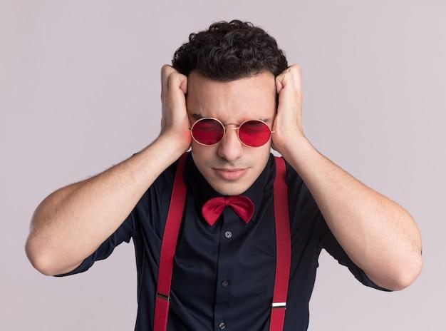 Stilvoller mann mit fliege, der brille und hosenträger trägt, die ohren mit hans mit genervtem ausdruck schließen, der über weißer wand steht