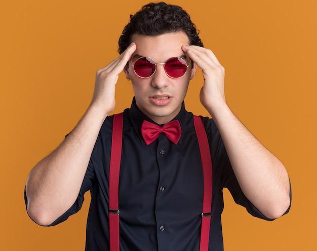 Stilvoller mann mit fliege, der brille und hosenträger trägt, die seinen kopf berühren, der unwohl sieht, das unter kopfschmerzen steht, die über orange wand stehen