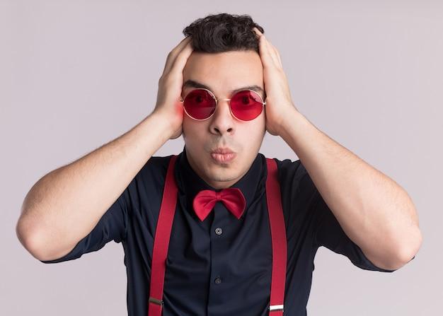 Stilvoller mann mit fliege, der brille und hosenträger trägt, die verwirrt und besorgt mit den händen auf seinem kopf betrachten, der über weißer wand steht