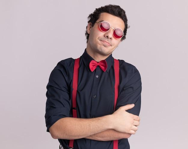 Stilvoller mann mit fliege, der brille und hosenträger trägt, die vorne mit skeptischem ausdruck mit verschränkten armen stehen, die über weißer wand stehen Kostenlose Fotos