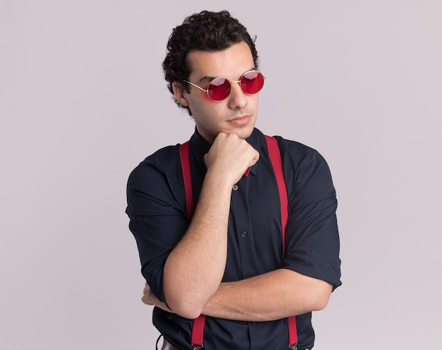 Stilvoller mann mit fliege, die brille und hosenträger trägt, die mit hand auf seinem kinn beiseite schauen und über weiße wand stehen