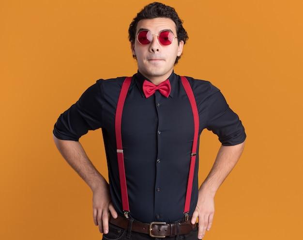 Stilvoller mann mit fliege, die brille und hosenträger trägt, die vorne betrachtet werden, verwirrt über orange wand stehend Kostenlose Fotos