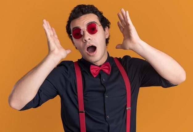 Stilvoller mann mit fliege, die brille und hosenträger trägt, die vorne erstaunt und überrascht über orange wand stehen