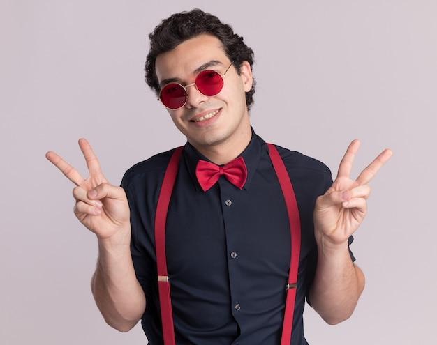 Stilvoller mann mit fliege, die brille und hosenträger trägt, die vorne mit einem lächeln auf gesicht schauen, das v-zeichen zeigt, das über weißer wand steht