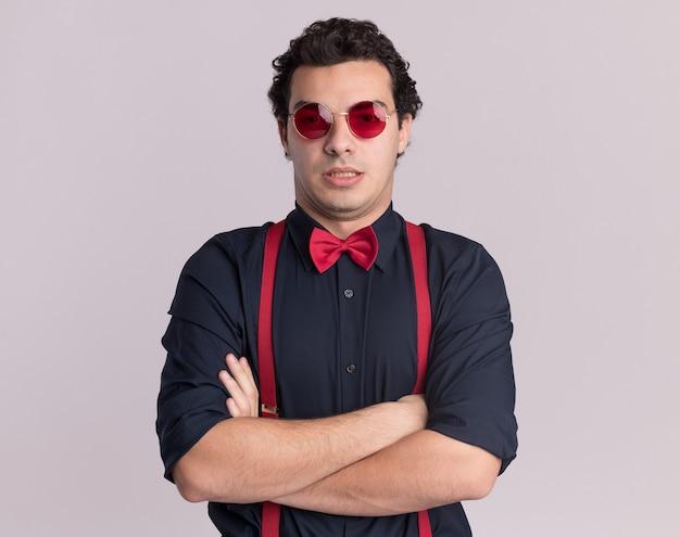 Stilvoller mann mit fliege, die brille und hosenträger trägt, die vorne mit ernstem gesicht mit verschränkten armen stehen, die über weißer wand stehen Kostenlose Fotos