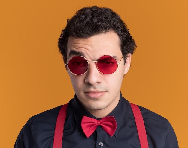 Stilvoller mann mit fliege, die brille und hosenträger trägt, die vorne mit skeptischem ausdruck stehen, der über orange wand steht Kostenlose Fotos