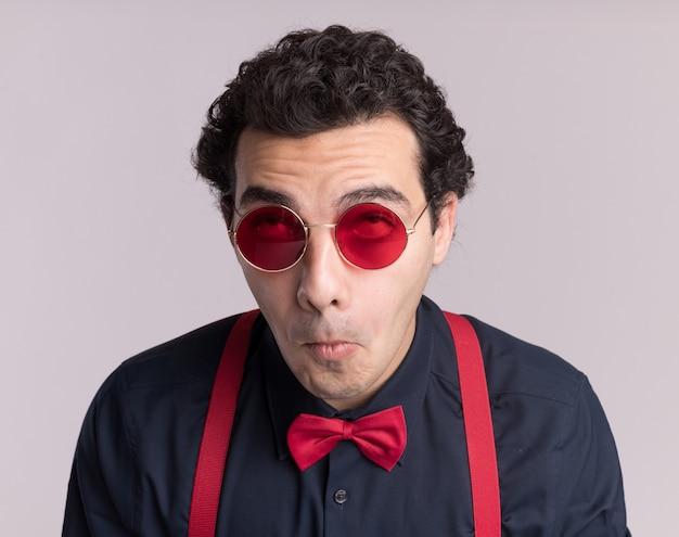 Stilvoller mann mit fliege, die brille und hosenträger trägt, rollt die augen hoch über weißer wand Kostenlose Fotos
