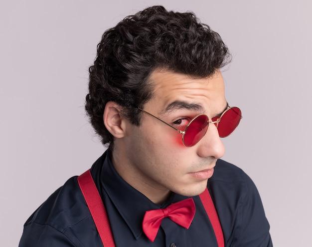 Stilvoller mann mit fliege, die brille und hosenträger trägt, schaut vorne mit skeptischem ausdruck, der über weißer wand steht
