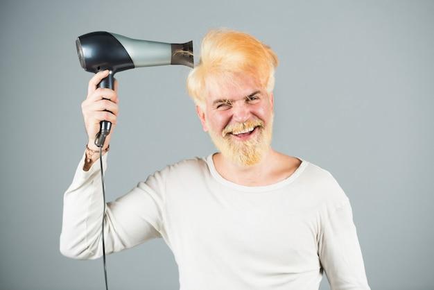 Stilvoller mann mit fön und lustigen ausdrücken im friseursalon. blondes bärtiges mannhaar trocken.