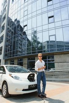 Stilvoller mann mit kaffeetasse in der hand steckt stecker in die ladebuchse des elektroautos