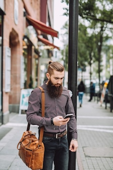 Stilvoller mann mit langem bart mit telefon