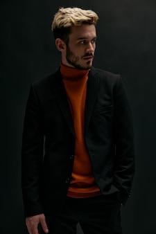 Stilvoller mann mit modischer frisur und in einem orangefarbenen pullover mit lederjacke auf schwarzem hintergrund