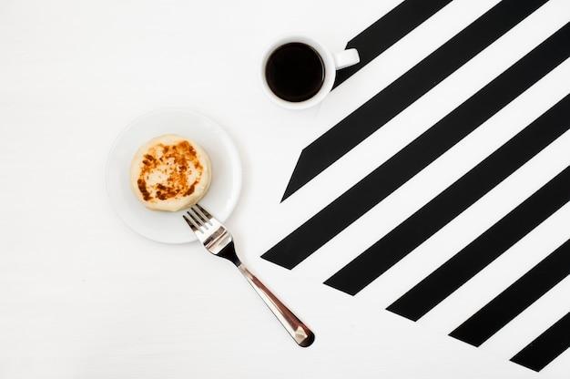 Stilvoller minimalistic arbeitsplatz mit tasse kaffee auf gestreiftem hintergrund