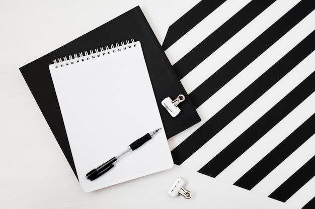 Stilvoller minimalistischer arbeitsplatz mit notizbuchspott oben, bleistift auf gestreiftem schwarzweiss-ba