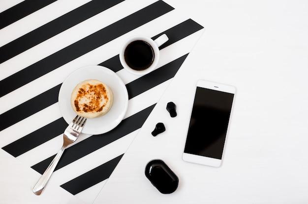 Stilvoller minimalistischer arbeitsplatz mit smartphone-spott oben, buch, notizbuch, bleistift, tasse kaffee