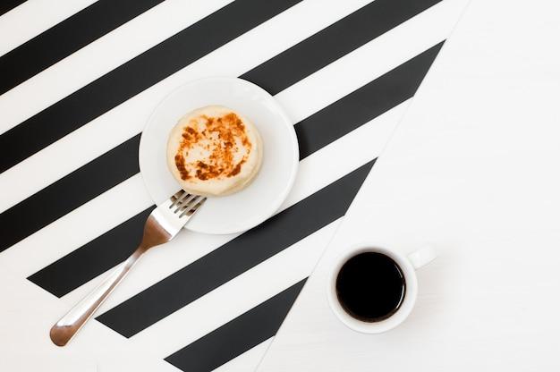 Stilvoller minimalistischer arbeitsplatz mit tasse kaffee und bäckerei