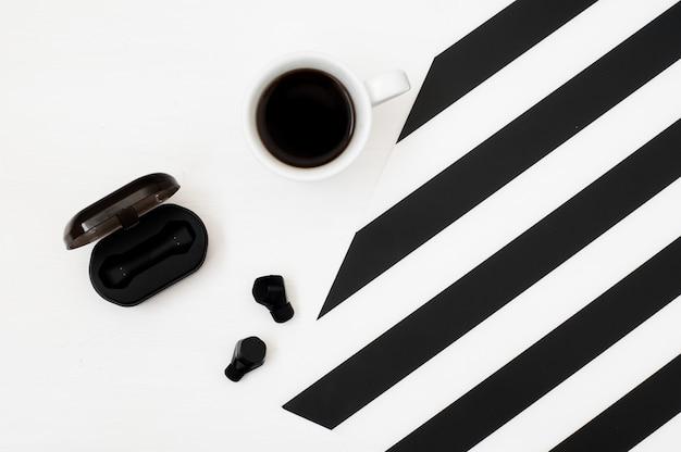 Stilvoller minimalistischer arbeitsplatz mit tasse kaffee und kabellosen kopfhörern